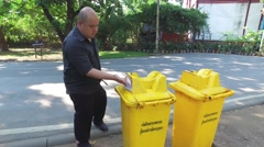 Fat bald head Asian Thai man find litter on the road and put it in the trash Stock Footage