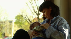 Mother breastfeeds baby, sitting near window Stock Footage