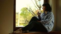 Woman drinks water, sitting on windowsill - stock footage