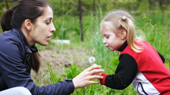 Mother and daughter blowing blowball Stock Footage