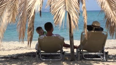 Family resting on lounges under palm tree, admiring seascape Stock Footage