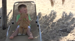 Little child and teddy bear toy summer love, blond hair boy on sunbed play, hugg Stock Footage