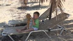Little boy on lounge on beach playing with thirsty teddy bear toy, give water - stock footage