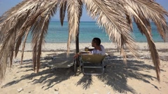 Young man laying an a sunbed at palm shadow, drinking fresh drink and admire sea Stock Footage