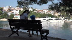 Beautiful mother and little child on bench, boat floating on sea, white town Stock Footage