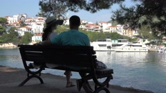 Romantic couple resting on a bench at a pine tree shadow, port, white village  Stock Footage