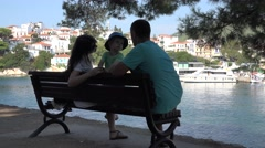 Beautiful family sitting on the beach and admiring white village, summer holiday Stock Footage