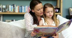 A mother is reading a book to her daughter Arkistovideo