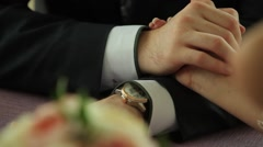 Bride and groom holding hands, dynamic change of focus on bouquet flowers Stock Footage