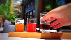4K Vignette Shot, Beer Tasting Flight, Macro Shot of Hand at Pub, Summer Sun - stock footage