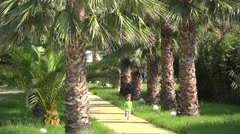 Happy child with blond hair running on palm trees alley, enjoying exotic holiday Stock Footage