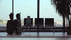 Funny child sitting on  waiting chair in airport, restless toddler passenger Stock Footage