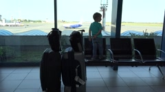 Child in airport standing on chair, looking restless at the window Stock Footage