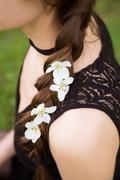 Close up view of young woman's tress with flowers - stock photo