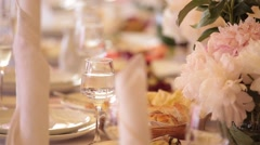 The elegant wedding or birthday dinner table with flowers, close up Stock Footage