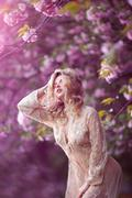 Beautiful sexy adult girl standing at blossoming tree in the garden - stock photo