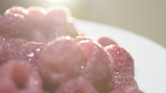 Closeup shot of vibrant, ripe raspberries in the morning light. - stock footage