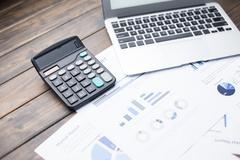 Laptop and calculator on financial report Stock Photos