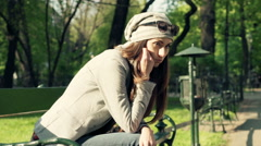 Sad, unhappy hipster woman sitting on bench in city park - stock footage