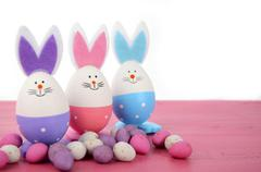 Easter eggs with bunny ears on pink table. - stock photo