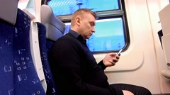 Man uses a smartphone in a compartment of a passenger train - stock footage