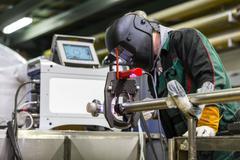 Industrial worker setting orbital welding machine. - stock photo