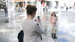 Milan Piazza Gae Aulenti Fountain - Parents makes photo of Daughter by Phone Stock Footage