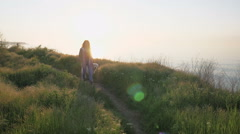 Young female walking with retriever dog on path near the sea at sunset Stock Footage