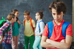 Offended schoolboy on background of chatting pupils - stock photo