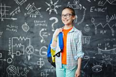 Clever schoolgirl with blue backpack on background of blackboard - stock photo