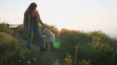 Young girl teasing retriever dog  on the path near the sea at sunset  Stock Footage