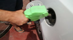 Man counting dollar bills as he refuel his car - stock footage