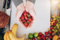 Woman holding a handful of fresh strawberries - stock photo