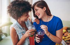 Cheerful young friends having fresh juice - stock photo
