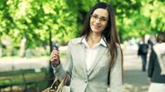 Portrait of happy, elegant woman walking in city park Stock Footage