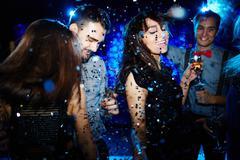 Glamorous friends dancing in confetti - stock photo