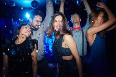 Ecstatic young woman and her posh dancing in night club Stock Photos