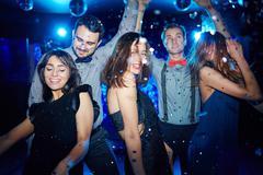 Posh girls and their boyfriends dancing in night club Stock Photos