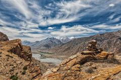 View of valley in Himalayas with stone cairn on cliff Stock Photos