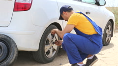 Side view of man fixing flat tire Stock Footage