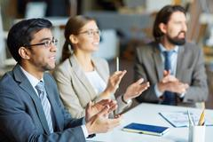 Group of satisfied managers applauding to speaker at conference Stock Photos