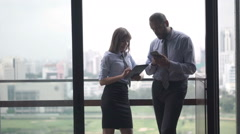 Shocked businesspeople reading bad news on tablet computer standing on terrace - stock footage