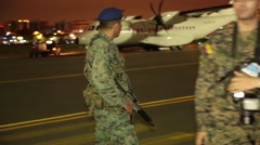 Soldier walking with an assault rifle on the tarmac in Ecuador Stock Footage
