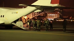 Soldiers in Ecuador boarding large FAE-1032 military transport plane at night Stock Footage