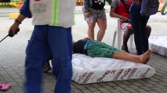 Woman laying on a make shift bed being seen by a doctor after the 2016 Ecuador - stock footage
