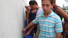 A large line of people filling up gallons of water in Ecuador after quake (3) - stock footage