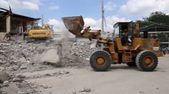 Bull dozers picking up rubble from destroyed building after 2016 Ecuador quake Stock Footage