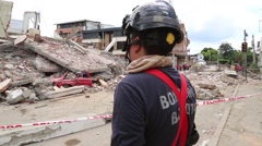 An Emergency worker looking on at a completely destroyed building, Ecuador quake Stock Footage