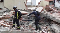 Personnel walking through rubble, 2016 Ecuador quake Stock Footage
