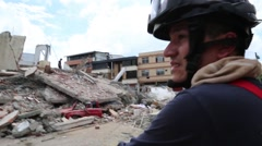 Up tilt from a car crushed by collapsed building to a fire fighter, 2016 Ecuador - stock footage